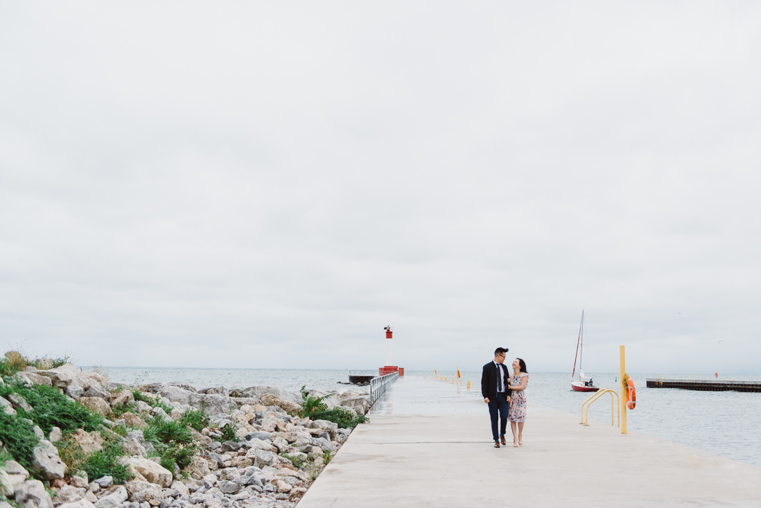 Couple walking along pier | Oakville Lakeside Park Engagement | EightyFifth Street Photography