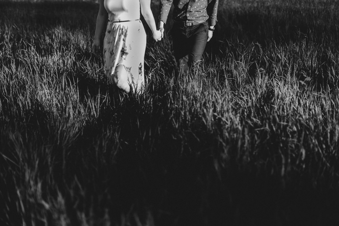 Moody black & white photo of couple walking in tall grass | Toronto Wedding Photographer | EightyFifth Street Photography