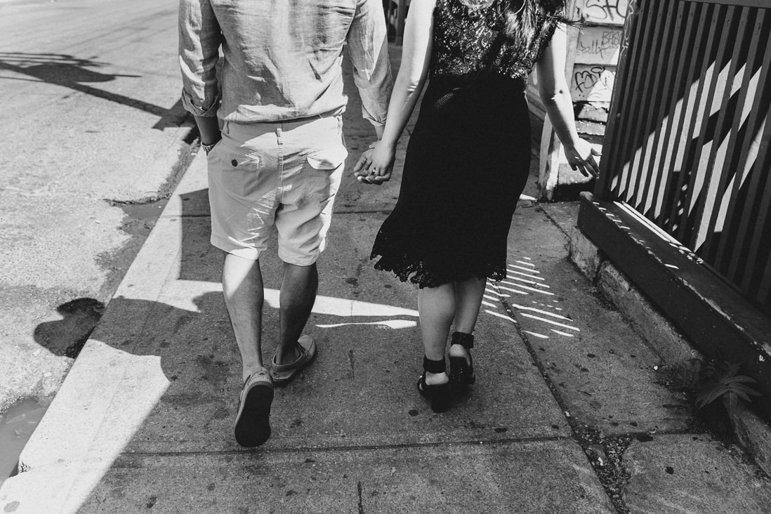 Black & White photo of couple walking on sidewalk | Kensington Market Engagement, Toronto | EightyFifth Street Photography