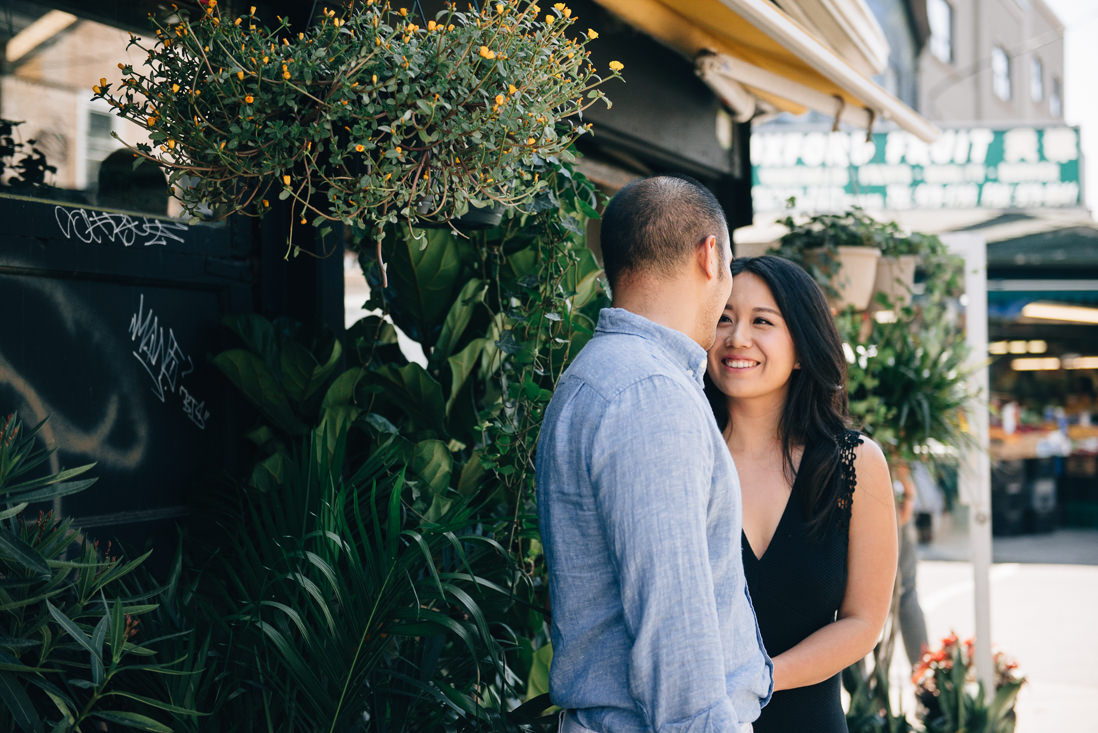 Couple laughing in front of plant shop | Kensington Market Engagement, Toronto | EightyFifth Street Photography
