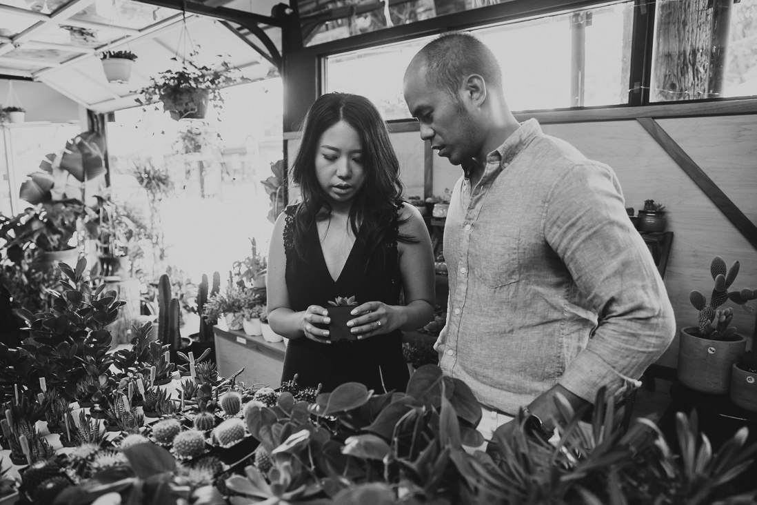 Black & White photo of couple shopping for cacti | Couple laughing in front of plant shop | Kensington Market Engagement, Toronto | EightyFifth Street Photography