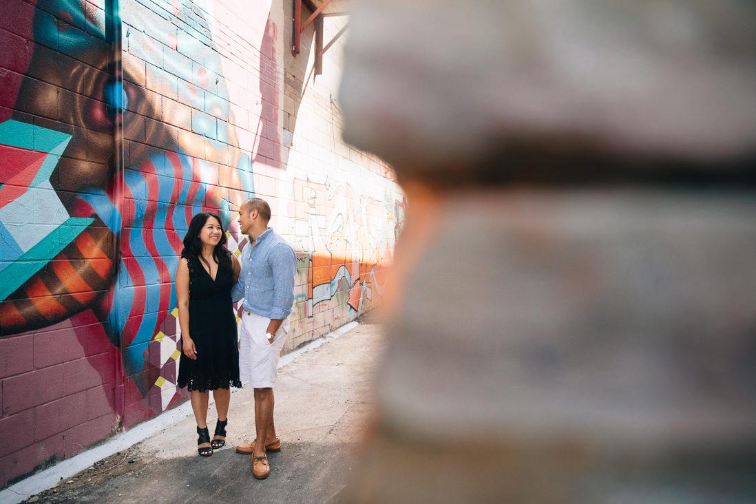 Couple laughing in graffiti alleyway   Kensington Market Engagement, Toronto   EightyFifth Street Photography