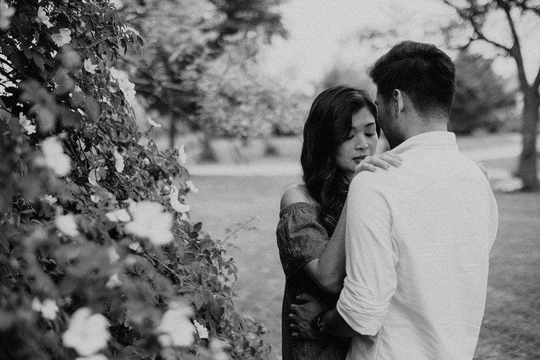 Black & white photo of Woman hugging fiance in front of flowering bush | Humber Bay Park Engagement Etobicoke | EightyFifth Street Photography