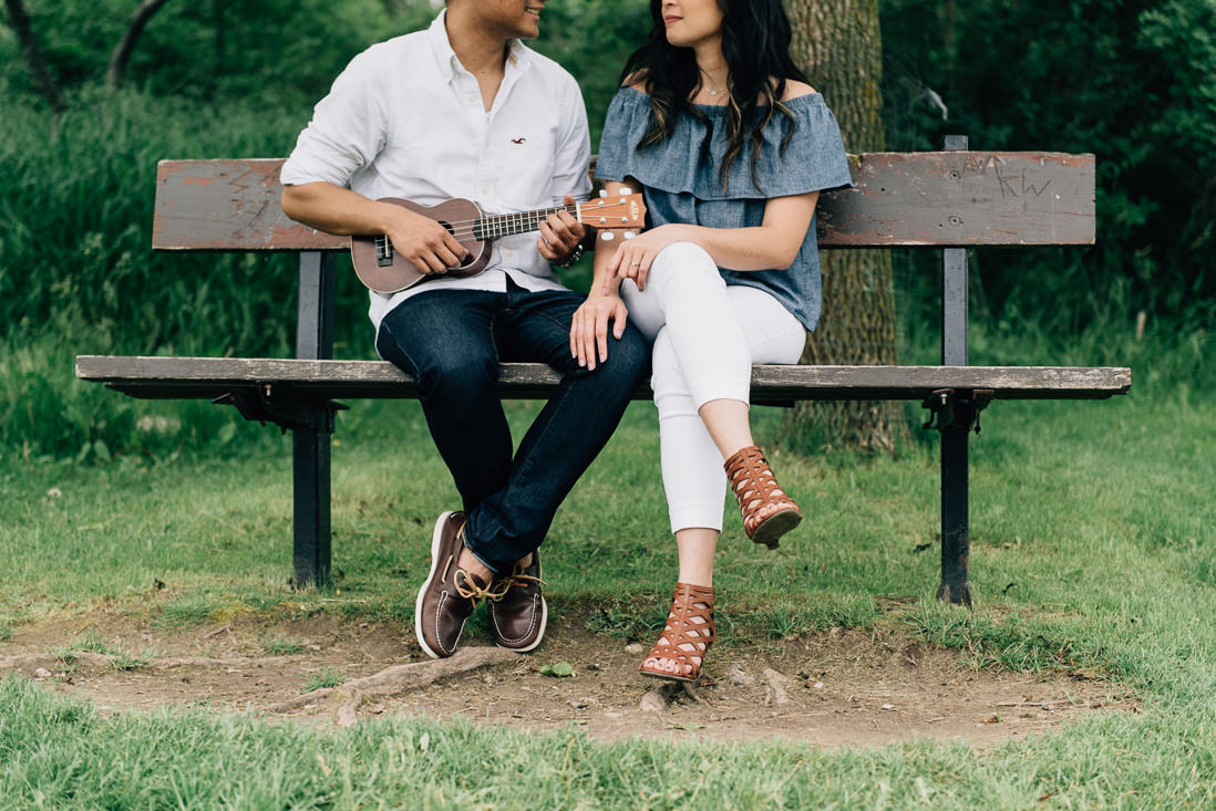 Man playing ukulele on a bench with girlfriend | Humber Bay Park Engagement Etobicoke | EightyFifth Street Photography