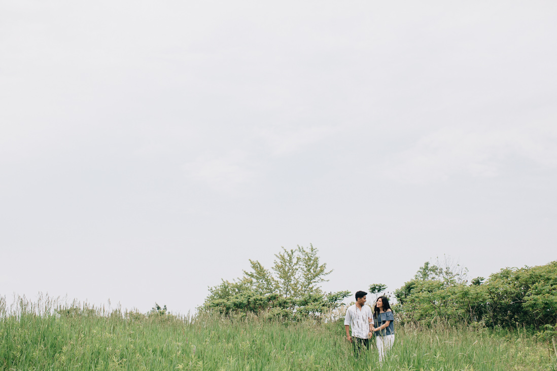 Couple walking through a field of grass from a distance | Humber Bay Park Engagement | EightyFifth Street Photography