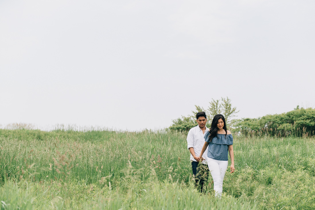 Couple walking through a field of grass | Humber Bay Park Engagement | EightyFifth Street Photography