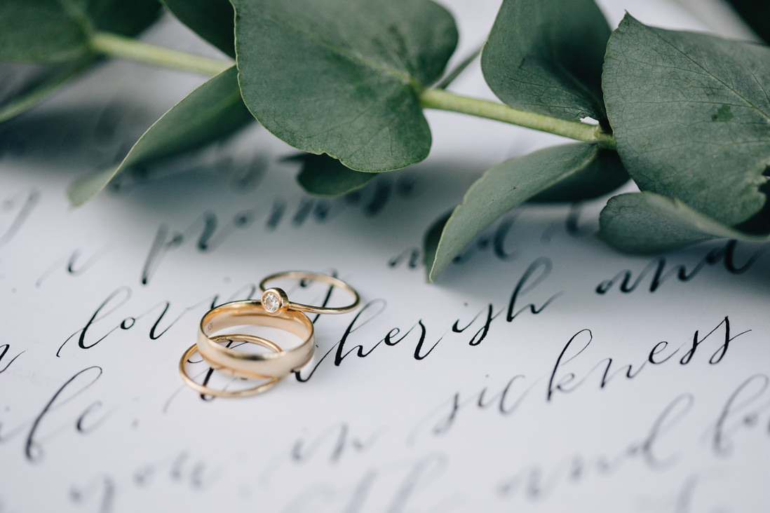 minimalist wedding rings on top of modern calligraphy vows | eightyfifth street photography