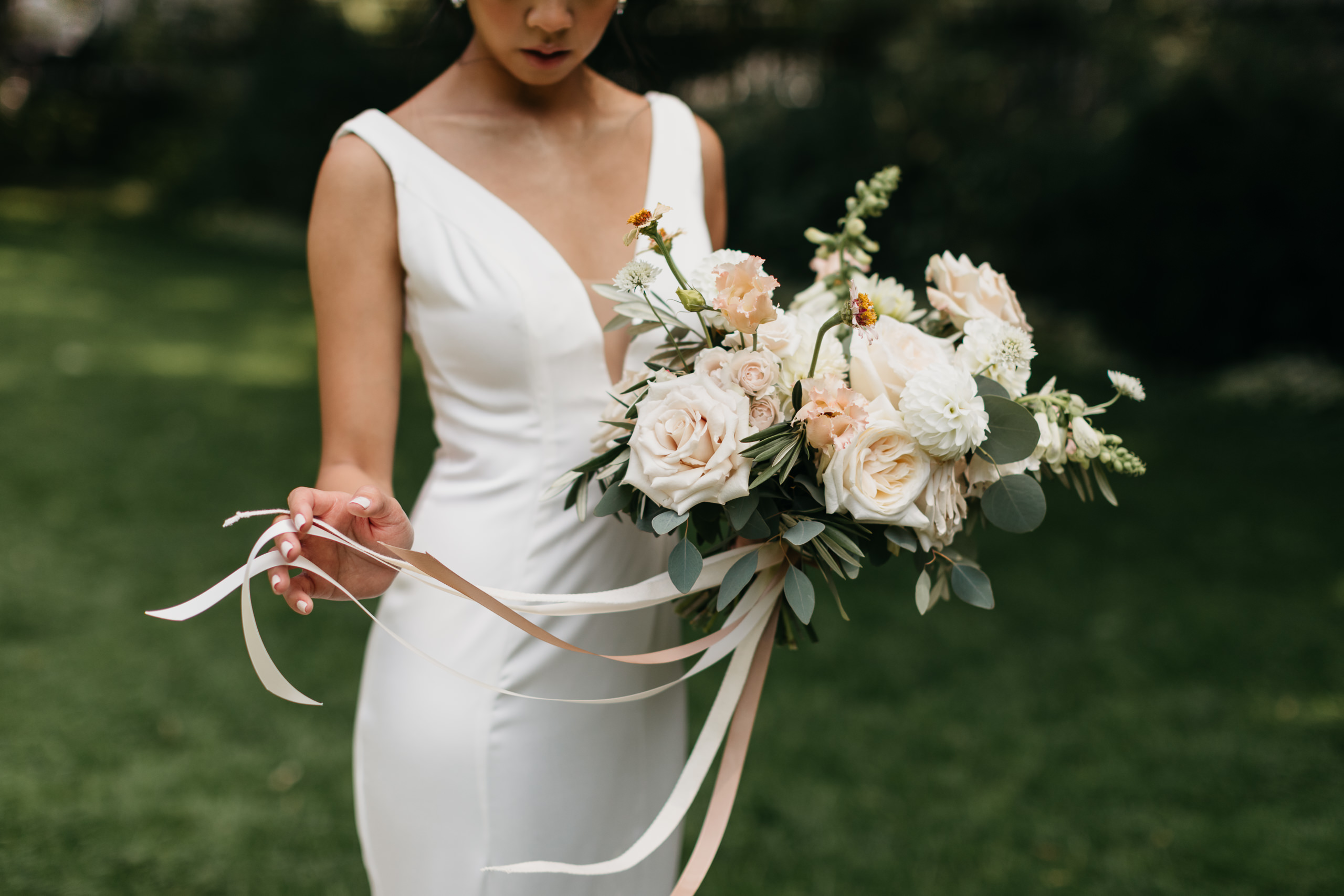 Bride with white and peach bouquet with ribbons by Coriander Girl at osgoode hall toronto wedding eightyfifth street photography