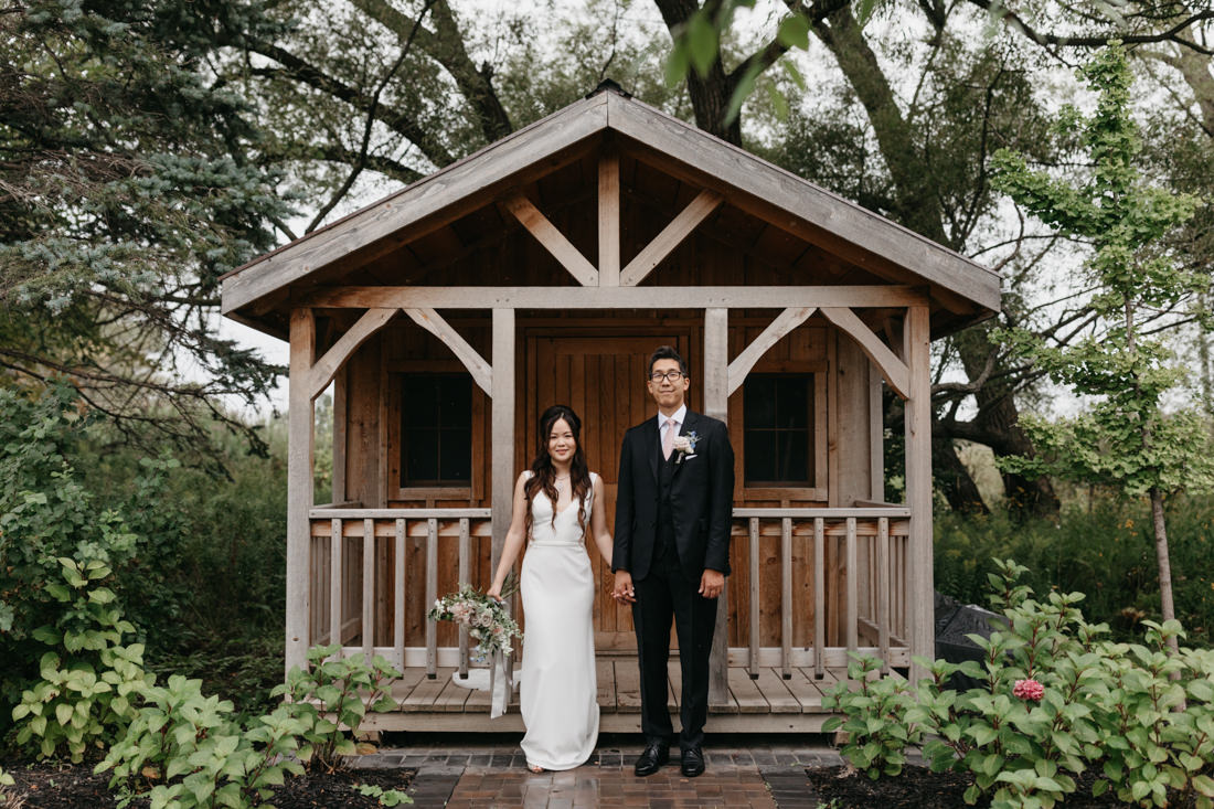 Bride & Groom standing in front of small cabin at arlington estate wedding in vaughan, ontario
