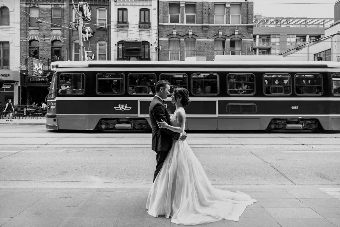 black & white portrait of bride & groom in front of passing street car on king st toronto wedding