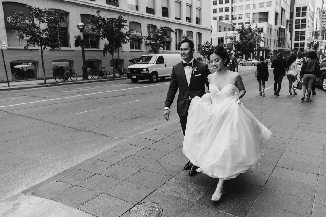 black and white bride & groom portrait walking on toronto streets