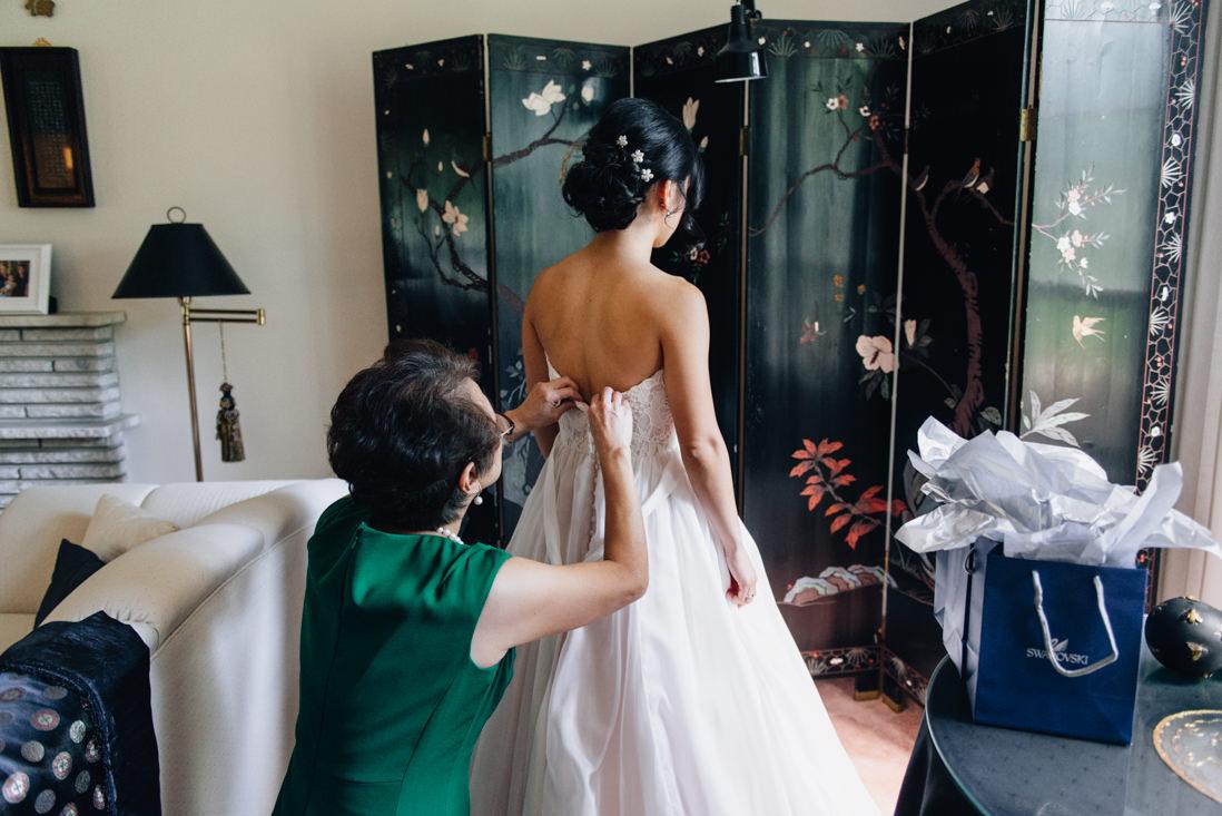 mother helping bride put on wedding dress toronto