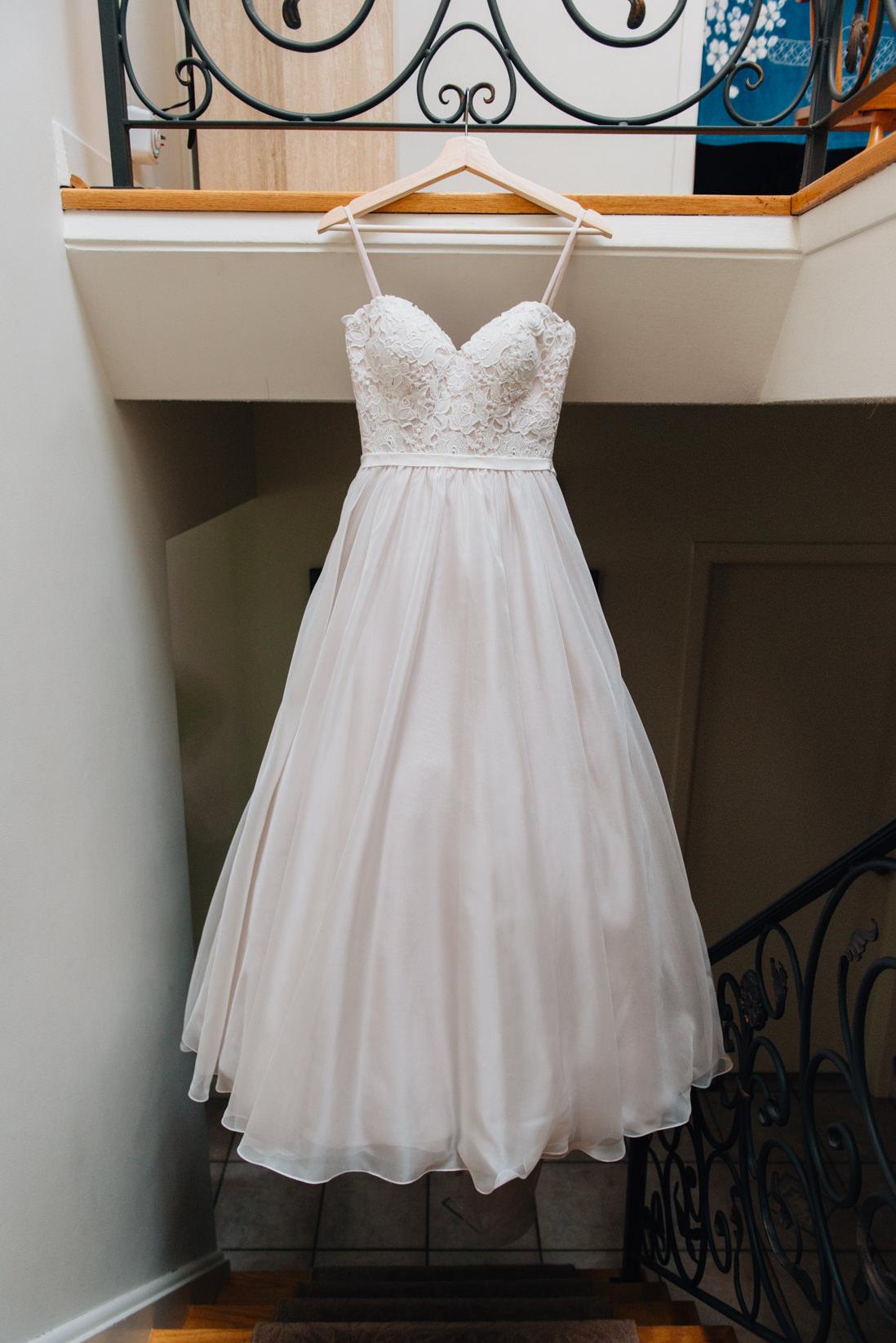 essense of australia wedding dress hanging in stairwell | eightyfifth street photography