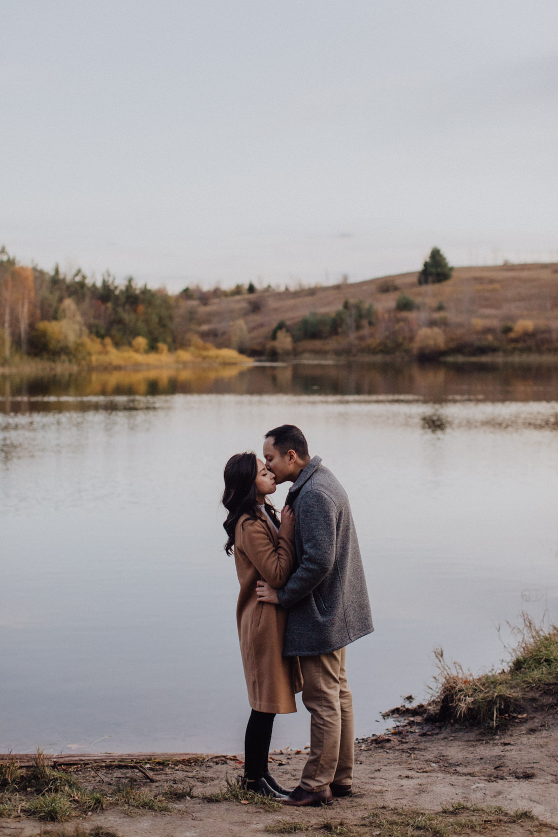 couple kissing in front of still lake fall engagement | eightyfifth street photography
