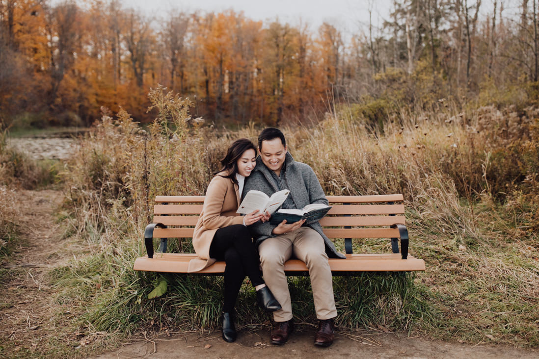 couple reading books on a bench fall engagement caledon | eightyfifth street photography