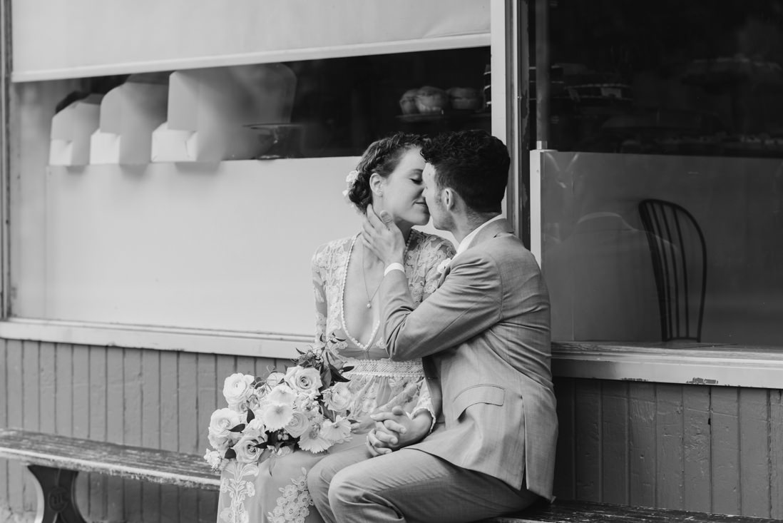 bride and groom kissing in front of bakery Toronto_EightyFifth Street Photography