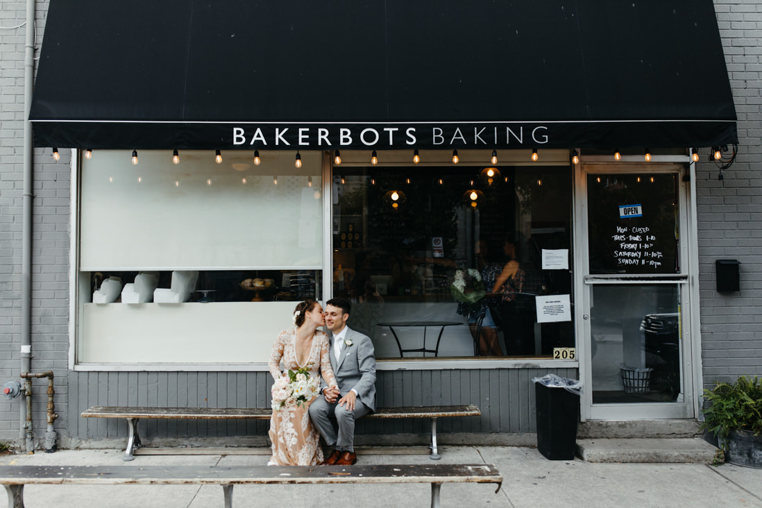 bride and groom sitting in front of bake shop Toronto_EightyFifth Street Photography